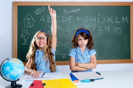 Smart nerd student in classroom raising hand