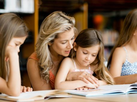 Little girls with their mother reading books