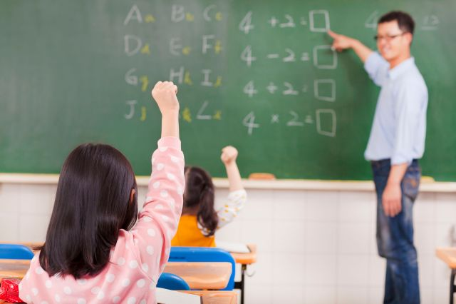 elementary school students raising hands